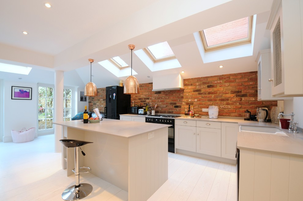 Example of a danish l-shaped light wood floor kitchen design in London with a farmhouse sink, shaker cabinets, white cabinets, black appliances and an island