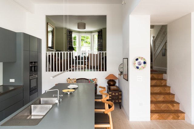 Medium sized contemporary u-shaped open plan kitchen in London with an integrated sink, flat-panel cabinets, grey cabinets, composite countertops, blue splashback, glass sheet splashback, stainless steel appliances, light hardwood flooring, an island and beige floors.