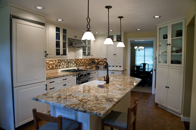Inspiration for a large timeless l-shaped concrete floor eat-in kitchen remodel in Seattle with a farmhouse sink, raised-panel cabinets, white cabinets, granite countertops, multicolored backsplash, mosaic tile backsplash, paneled appliances and an island