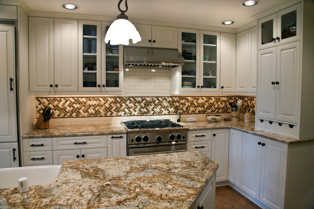 Example of a large classic l-shaped concrete floor eat-in kitchen design in Seattle with a farmhouse sink, raised-panel cabinets, white cabinets, granite countertops, multicolored backsplash, mosaic tile backsplash, paneled appliances and an island