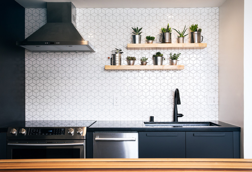 Inspiration for a small contemporary galley concrete floor and gray floor kitchen remodel in San Francisco with an undermount sink, flat-panel cabinets, quartzite countertops, white backsplash, ceramic backsplash, stainless steel appliances and black countertops