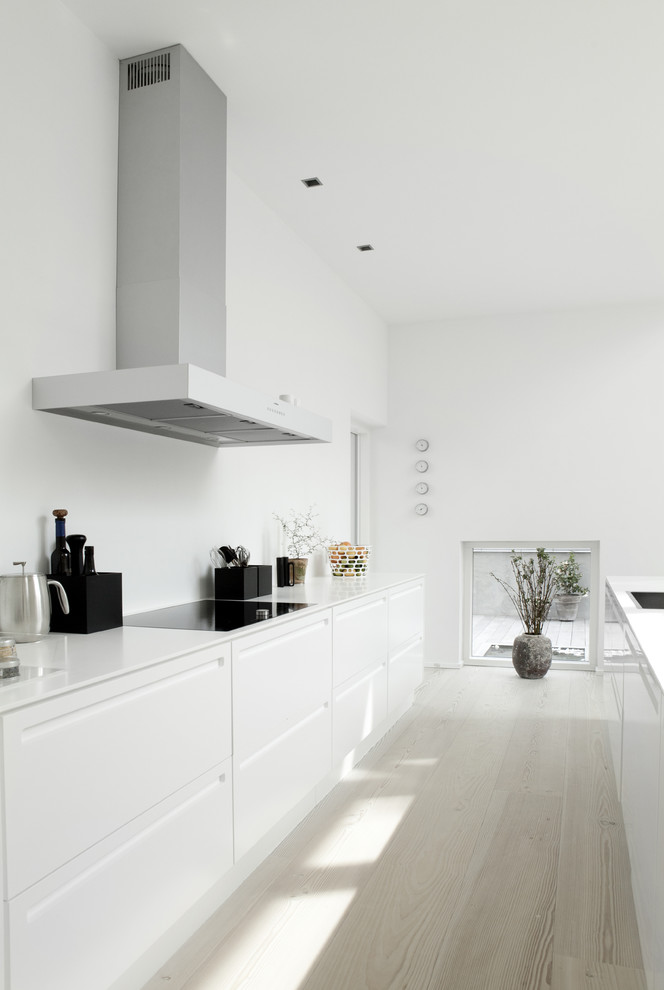 Example of a danish galley light wood floor and white floor kitchen design in West Midlands with flat-panel cabinets, white cabinets and an island