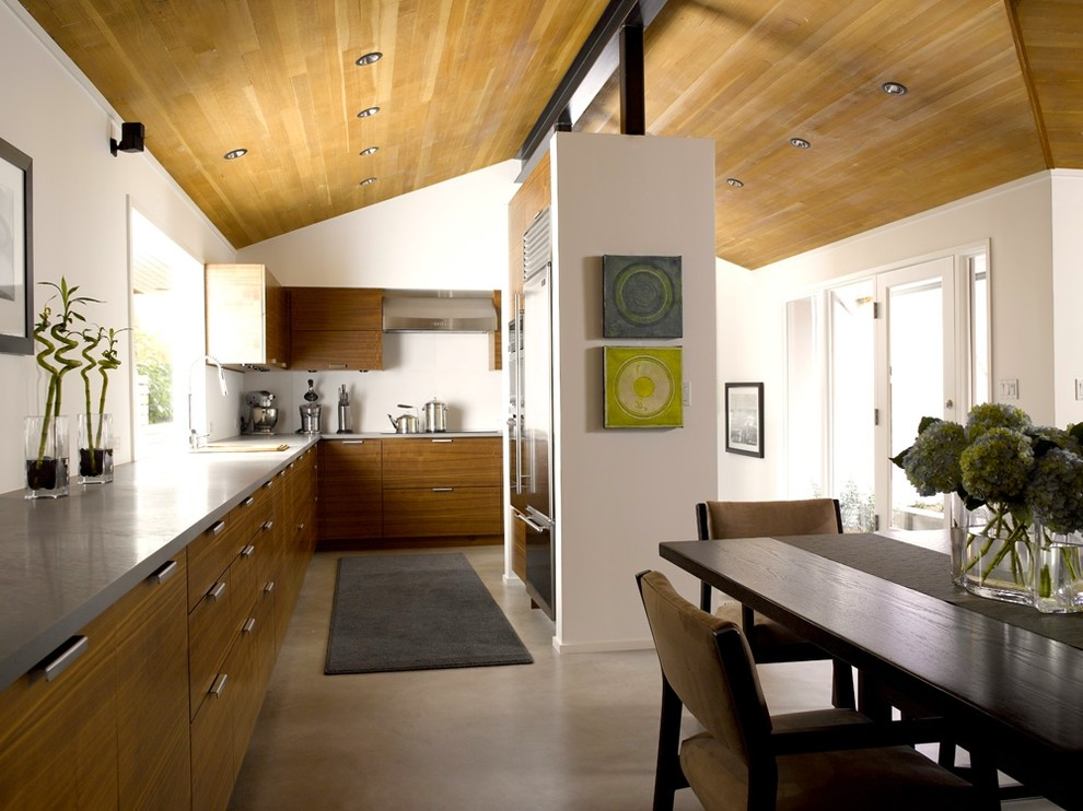 Mid-sized trendy l-shaped concrete floor and gray floor eat-in kitchen photo in Seattle with stainless steel appliances, an undermount sink, flat-panel cabinets, medium tone wood cabinets, concrete countertops, no island and gray countertops
