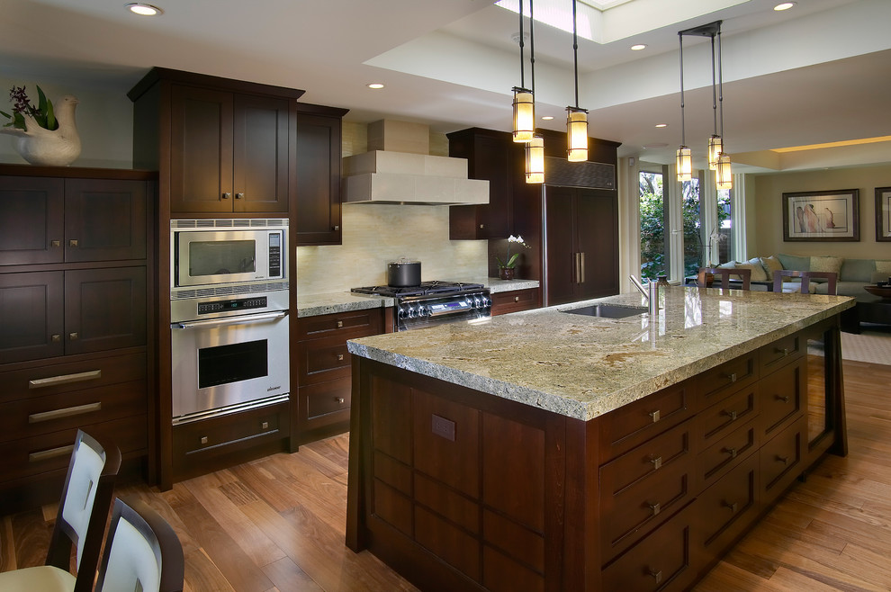 Example of a large trendy l-shaped medium tone wood floor and brown floor open concept kitchen design in San Diego with stainless steel appliances, an undermount sink, shaker cabinets, dark wood cabinets, granite countertops, beige backsplash, stone slab backsplash and an island