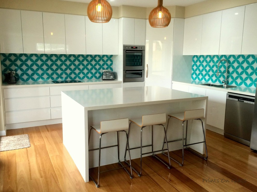 Inspiration for a modern kitchen in Sydney with glass sheet splashback.