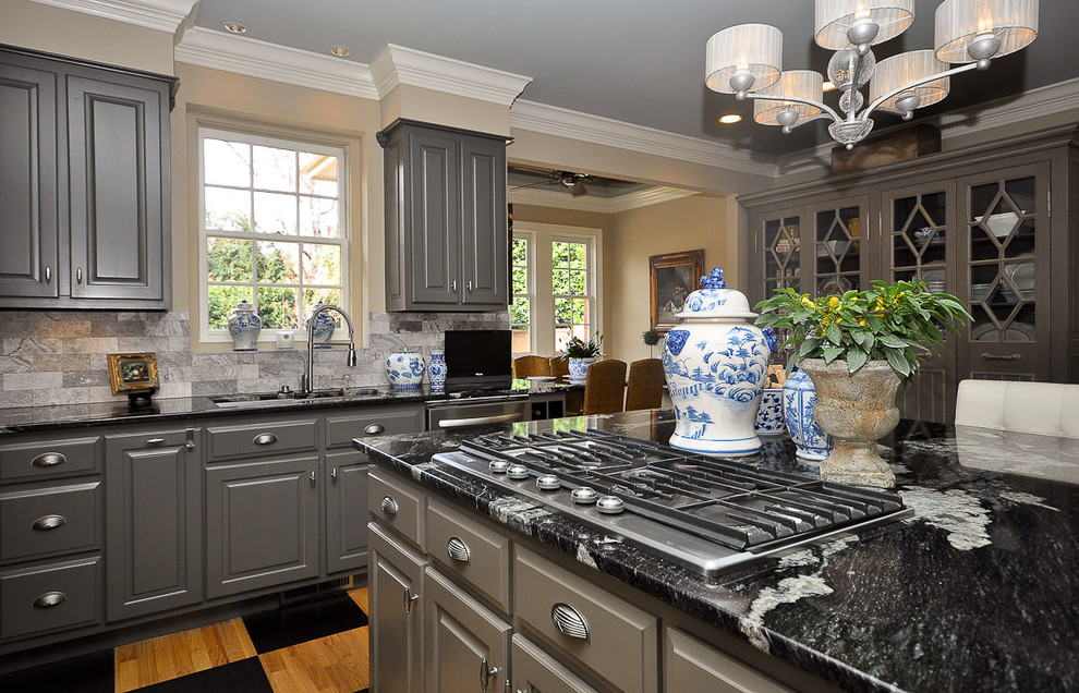 Kitchen - mid-sized traditional l-shaped kitchen idea in Other with an undermount sink, raised-panel cabinets, gray cabinets, gray backsplash, stainless steel appliances and an island