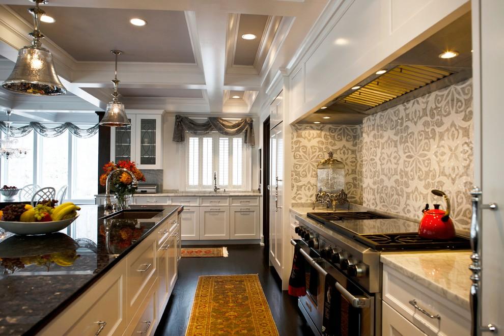 Large transitional u-shaped dark wood floor enclosed kitchen photo in Philadelphia with white cabinets, marble countertops, gray backsplash, mosaic tile backsplash, paneled appliances and an island
