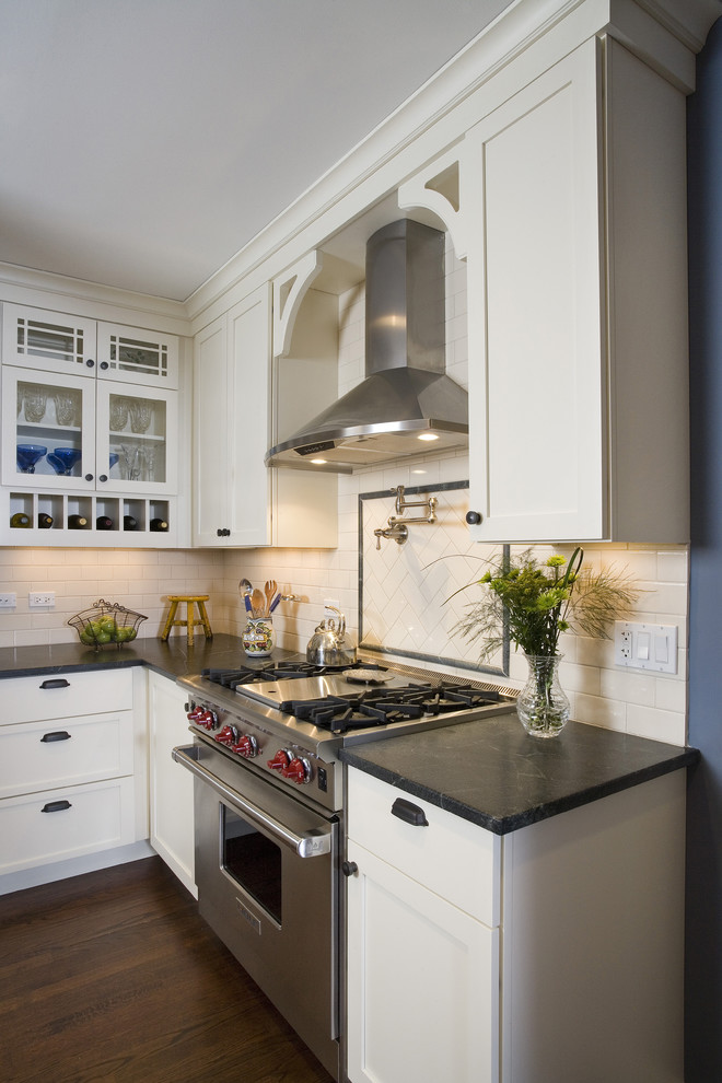Example of a mid-sized classic u-shaped medium tone wood floor and brown floor eat-in kitchen design in Chicago with stainless steel appliances, subway tile backsplash, soapstone countertops, white cabinets, white backsplash, glass-front cabinets, a farmhouse sink and white countertops