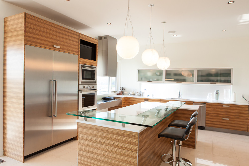 Example of a minimalist l-shaped kitchen design in Edmonton with stainless steel appliances, glass countertops, an undermount sink, flat-panel cabinets and medium tone wood cabinets
