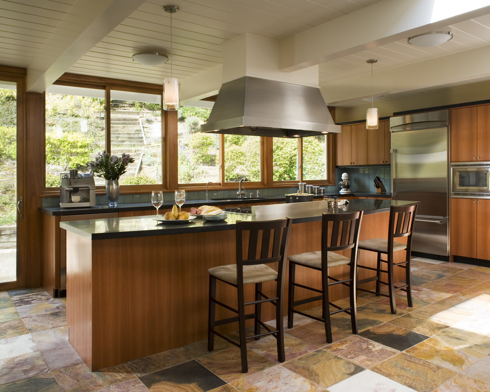 Trendy multicolored floor kitchen photo in San Francisco with flat-panel cabinets, medium tone wood cabinets, blue backsplash and stainless steel appliances