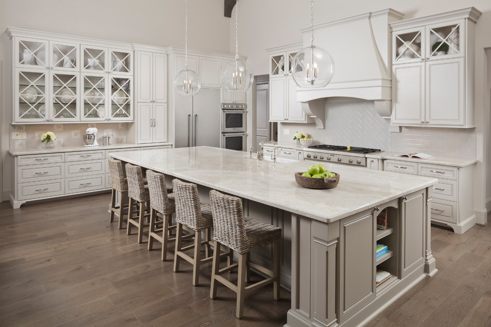 Elegant light wood floor and beige floor kitchen photo in Houston with a farmhouse sink, beige cabinets, beige backsplash, stainless steel appliances, an island, quartzite countertops and recessed-panel cabinets