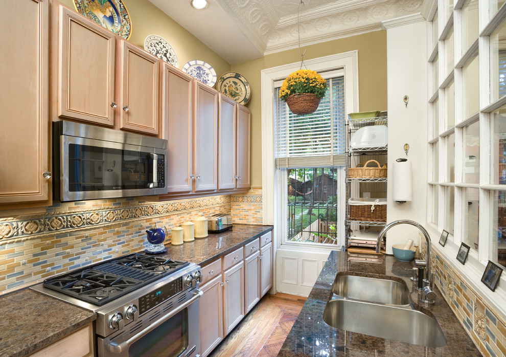 Inspiration for a timeless galley enclosed kitchen remodel in New York with a double-bowl sink, stainless steel appliances, recessed-panel cabinets, light wood cabinets and multicolored backsplash