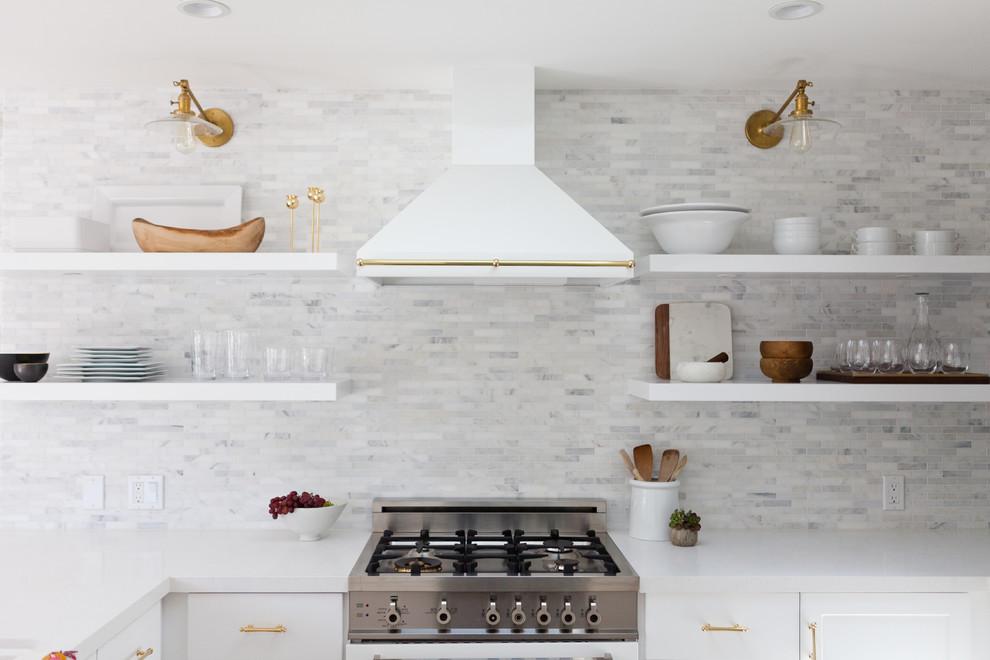 Modelo de cocina en U, marinera, de tamaño medio, abierta, sin isla, con fregadero encastrado, armarios con paneles empotrados, puertas de armario blancas, encimera de mármol, salpicadero blanco, salpicadero de azulejos de porcelana, electrodomésticos blancos y suelo de madera clara