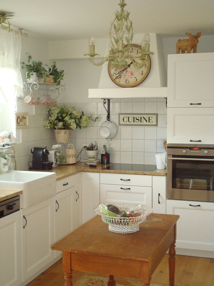 Example of a country kitchen design with stainless steel appliances and a farmhouse sink