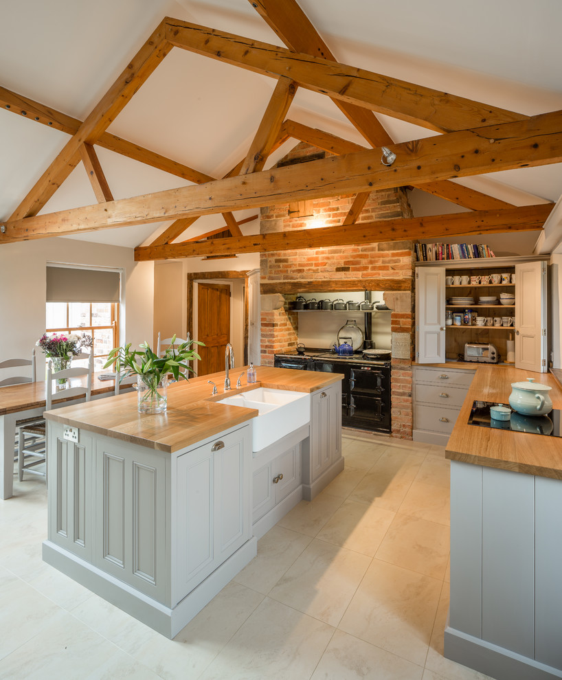 Inspiration for a large farmhouse l-shaped eat-in kitchen remodel in Other with a farmhouse sink, recessed-panel cabinets, gray cabinets, wood countertops and an island