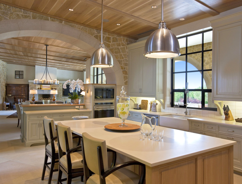 Open concept kitchen - large contemporary u-shaped limestone floor open concept kitchen idea in Austin with raised-panel cabinets, a double-bowl sink, white cabinets, stainless steel appliances, an island, solid surface countertops, white backsplash and subway tile backsplash