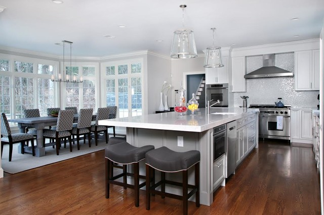 Large trendy l-shaped medium tone wood floor and brown floor eat-in kitchen photo in Other with a farmhouse sink, shaker cabinets, white cabinets, mosaic tile backsplash, stainless steel appliances, an island, marble countertops and gray backsplash