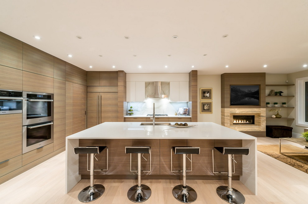 Large trendy l-shaped light wood floor open concept kitchen photo in Vancouver with an undermount sink, flat-panel cabinets, light wood cabinets, solid surface countertops, white backsplash, stone slab backsplash, stainless steel appliances and an island