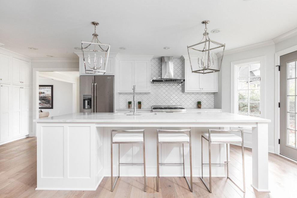 Example of a large transitional single-wall light wood floor and brown floor open concept kitchen design in Indianapolis with shaker cabinets, white cabinets, white backsplash, stainless steel appliances, an island, an undermount sink, quartz countertops and white countertops