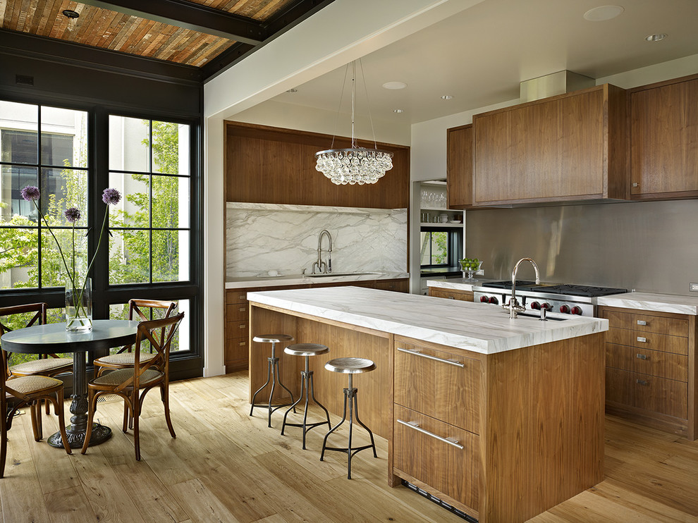 Example of a trendy kitchen design in Seattle with stainless steel appliances, flat-panel cabinets, dark wood cabinets, marble countertops, white backsplash and marble backsplash