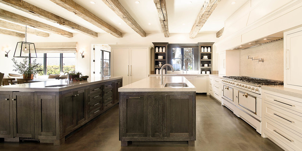 Huge cottage u-shaped concrete floor and brown floor eat-in kitchen photo in San Francisco with an undermount sink, shaker cabinets, white cabinets, beige backsplash, two islands, white appliances, quartz countertops and stone slab backsplash