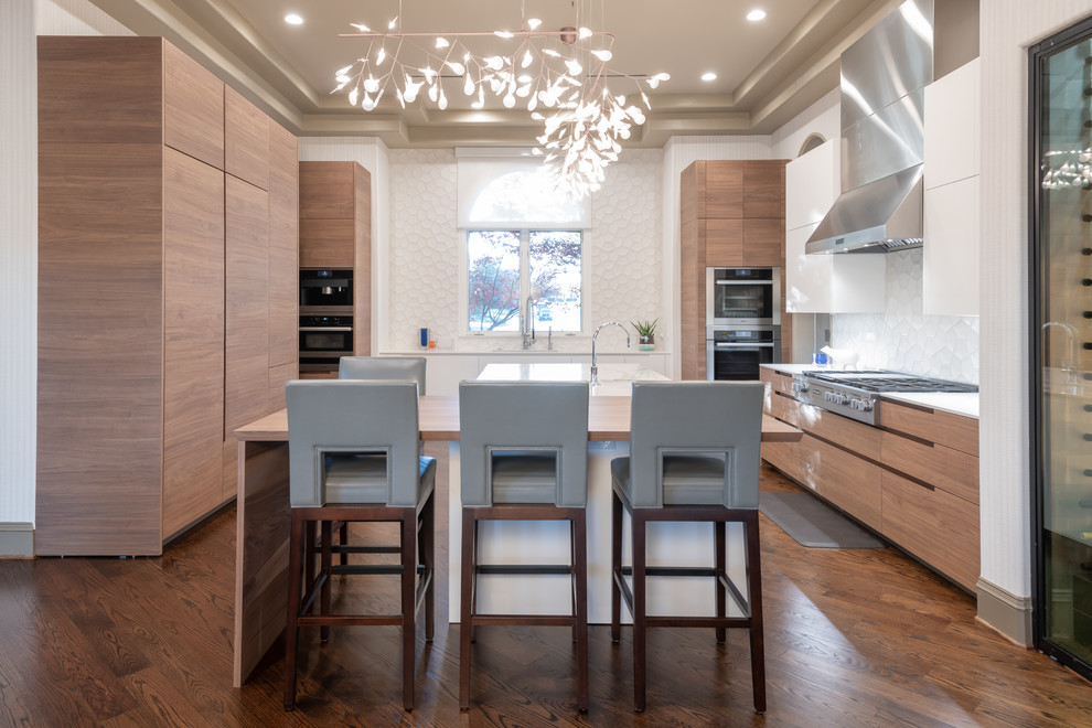 Inspiration for a large contemporary brown floor and dark wood floor kitchen remodel in Dallas with flat-panel cabinets, light wood cabinets, quartz countertops, white backsplash, cement tile backsplash, paneled appliances, an island and white countertops
