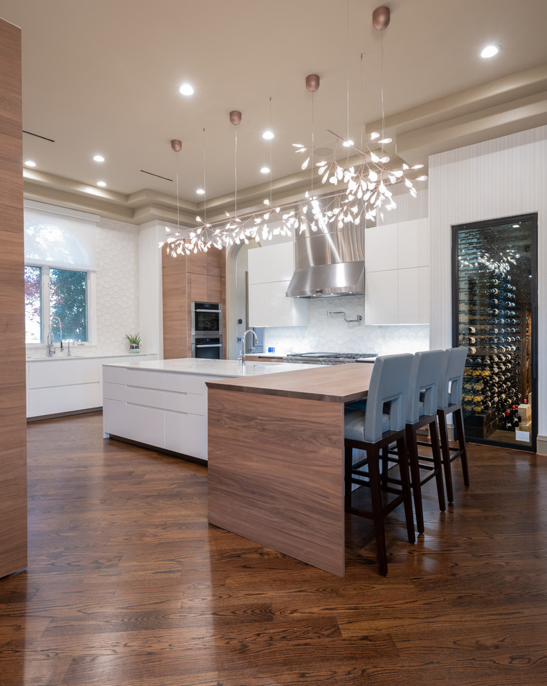 Example of a large trendy u-shaped medium tone wood floor and brown floor enclosed kitchen design in Dallas with a single-bowl sink, flat-panel cabinets, light wood cabinets, quartz countertops, white backsplash, cement tile backsplash, paneled appliances, an island and white countertops
