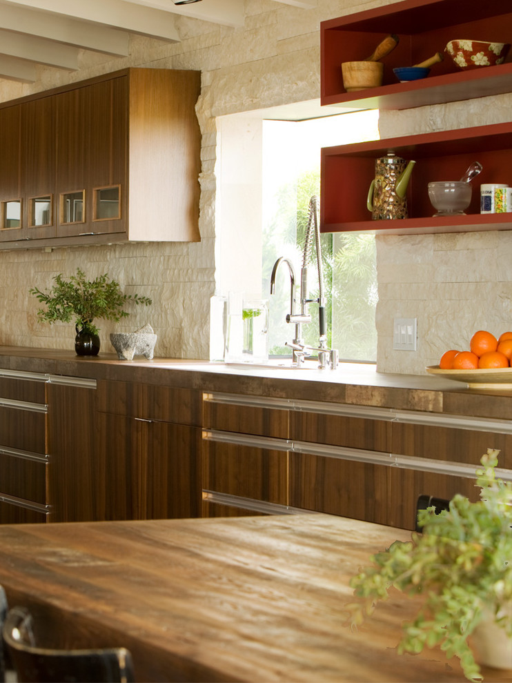Example of a 1950s kitchen design in Orange County with flat-panel cabinets, dark wood cabinets, wood countertops, beige backsplash and limestone backsplash