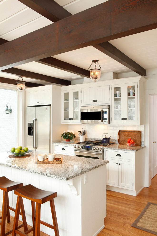 Inspiration for a small timeless single-wall medium tone wood floor and brown floor eat-in kitchen remodel in Other with glass-front cabinets, white cabinets, white backsplash, ceramic backsplash, stainless steel appliances, an island and granite countertops