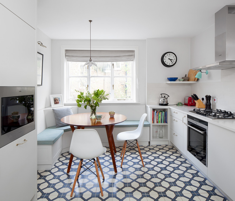 Example of a small trendy galley ceramic tile eat-in kitchen design in London with flat-panel cabinets, white cabinets and no island