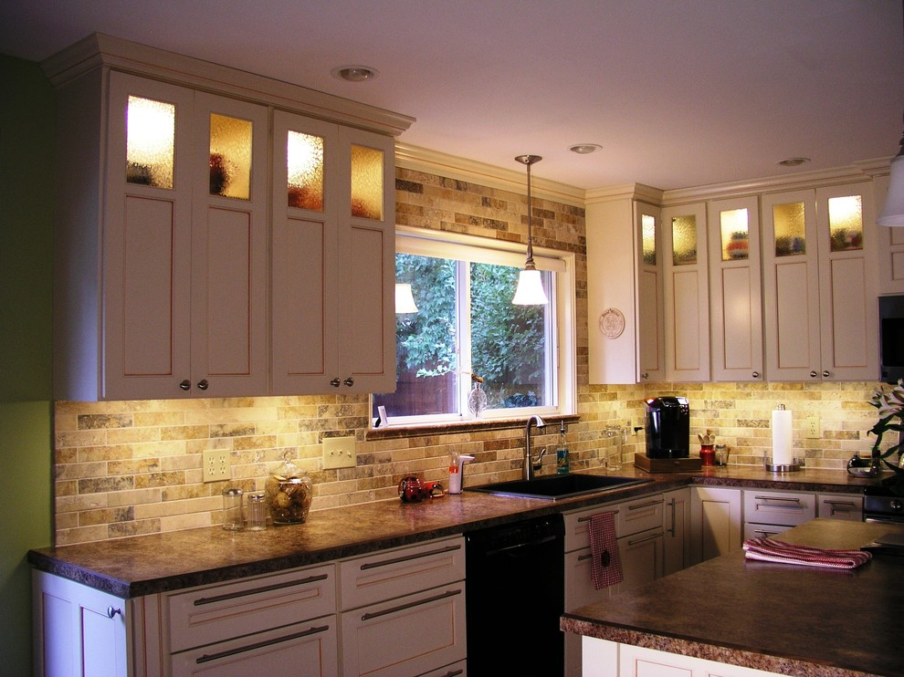 Open concept kitchen - large traditional l-shaped open concept kitchen idea in Phoenix with a drop-in sink, recessed-panel cabinets, beige cabinets, granite countertops, multicolored backsplash, subway tile backsplash, black appliances and an island