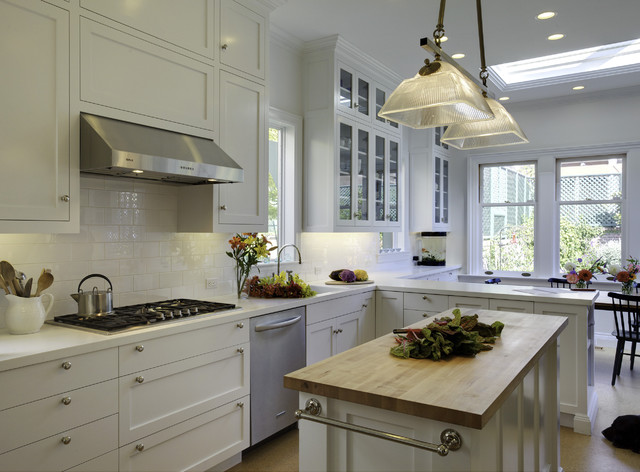 Example of a mid-sized classic l-shaped cork floor eat-in kitchen design in San Francisco with stainless steel appliances, subway tile backsplash, white cabinets, solid surface countertops, white backsplash, an island, a drop-in sink and shaker cabinets