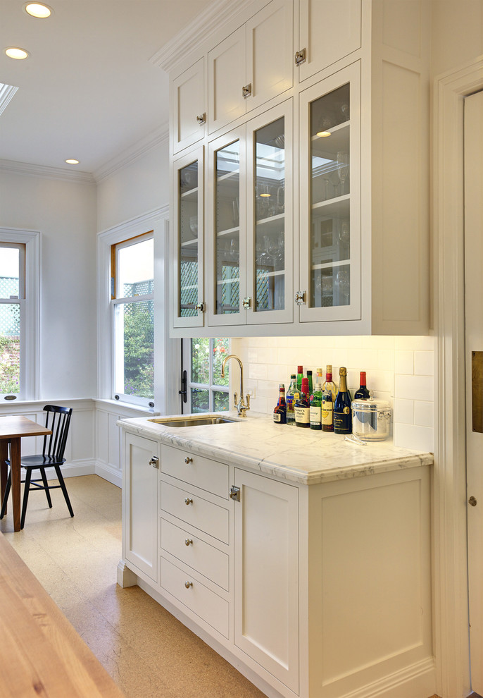 Eat-in kitchen - large traditional l-shaped cork floor eat-in kitchen idea in San Francisco with subway tile backsplash, an undermount sink, glass-front cabinets, white cabinets, white backsplash, marble countertops, stainless steel appliances and an island