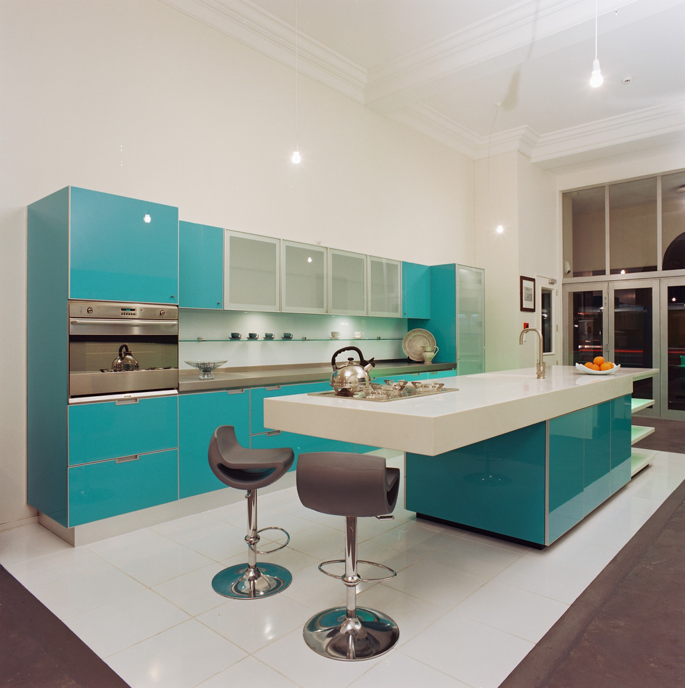 Trendy galley kitchen photo in Los Angeles with flat-panel cabinets, turquoise cabinets, solid surface countertops and stainless steel appliances