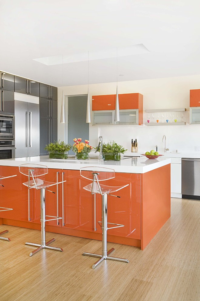 Kitchen - contemporary bamboo floor kitchen idea in San Francisco with stainless steel appliances, flat-panel cabinets, orange cabinets and quartz countertops