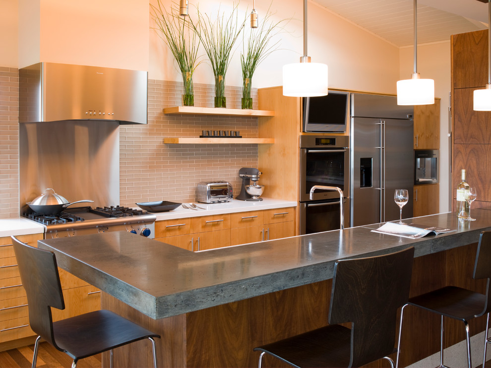 Example of a trendy kitchen design in San Francisco with stainless steel appliances, concrete countertops, flat-panel cabinets, light wood cabinets and gray backsplash
