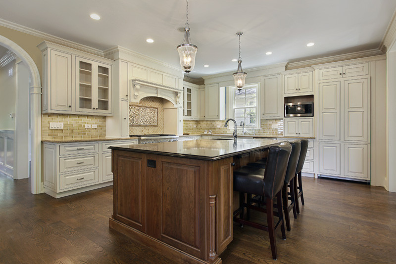 Mid-sized trendy u-shaped dark wood floor eat-in kitchen photo in Chicago with a double-bowl sink, raised-panel cabinets, white cabinets, soapstone countertops, beige backsplash, stone tile backsplash, stainless steel appliances and an island