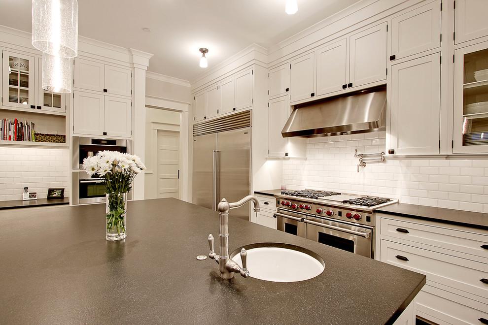 Diseño de cocina tradicional con armarios estilo shaker, electrodomésticos de acero inoxidable, fregadero bajoencimera, puertas de armario blancas, encimera de granito, salpicadero blanco, salpicadero de azulejos tipo metro, una isla y suelo de madera oscura