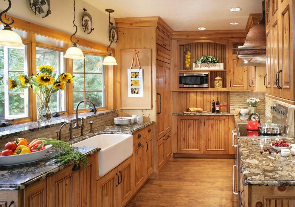 Elegant u-shaped enclosed kitchen photo in New York with a farmhouse sink, medium tone wood cabinets, granite countertops, beige backsplash and paneled appliances