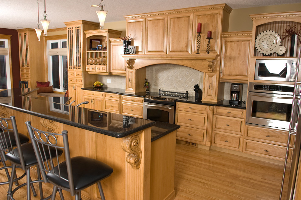 Open concept kitchen - mid-sized traditional l-shaped light wood floor open concept kitchen idea in Other with an undermount sink, raised-panel cabinets, light wood cabinets, granite countertops, beige backsplash, stainless steel appliances and an island