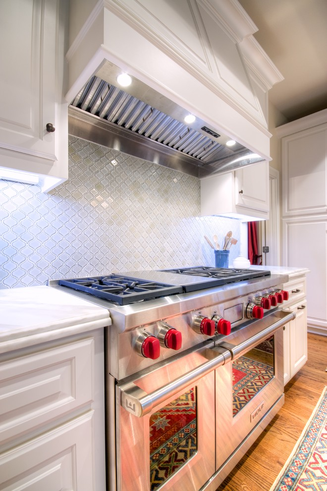 Inspiration for a large timeless l-shaped light wood floor eat-in kitchen remodel in Austin with raised-panel cabinets, white cabinets, marble countertops, white backsplash, glass tile backsplash, stainless steel appliances and an island