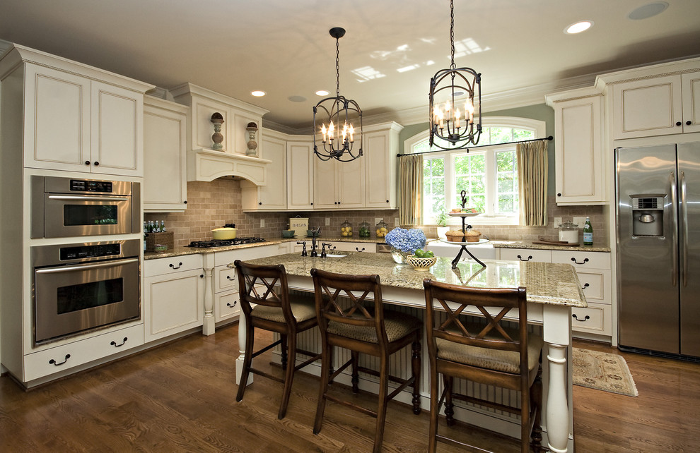 Elegant l-shaped kitchen photo in Raleigh with white cabinets, brown backsplash, stainless steel appliances and stone tile backsplash