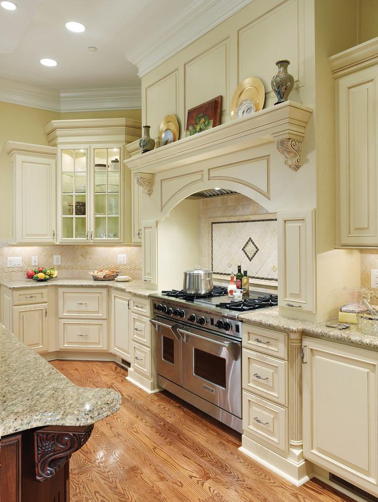 Large elegant medium tone wood floor and brown floor kitchen photo in DC Metro with raised-panel cabinets, white cabinets, granite countertops, beige backsplash, stone tile backsplash, paneled appliances and an island