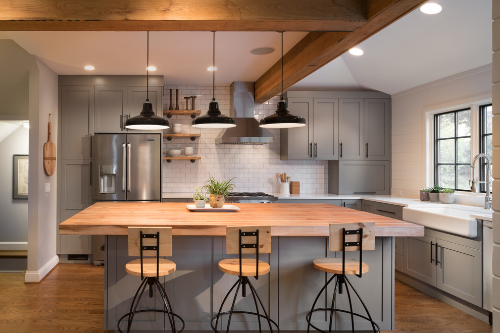 Inspiration for a large transitional l-shaped medium tone wood floor eat-in kitchen remodel in DC Metro with a farmhouse sink, shaker cabinets, gray cabinets, wood countertops, white backsplash, subway tile backsplash, stainless steel appliances and an island