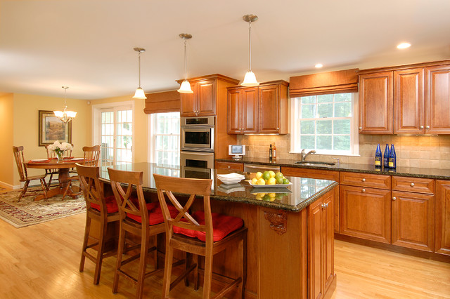 Example of a mid-sized trendy l-shaped light wood floor eat-in kitchen design in Boston with a drop-in sink, recessed-panel cabinets, medium tone wood cabinets, granite countertops, beige backsplash, cement tile backsplash, stainless steel appliances and an island