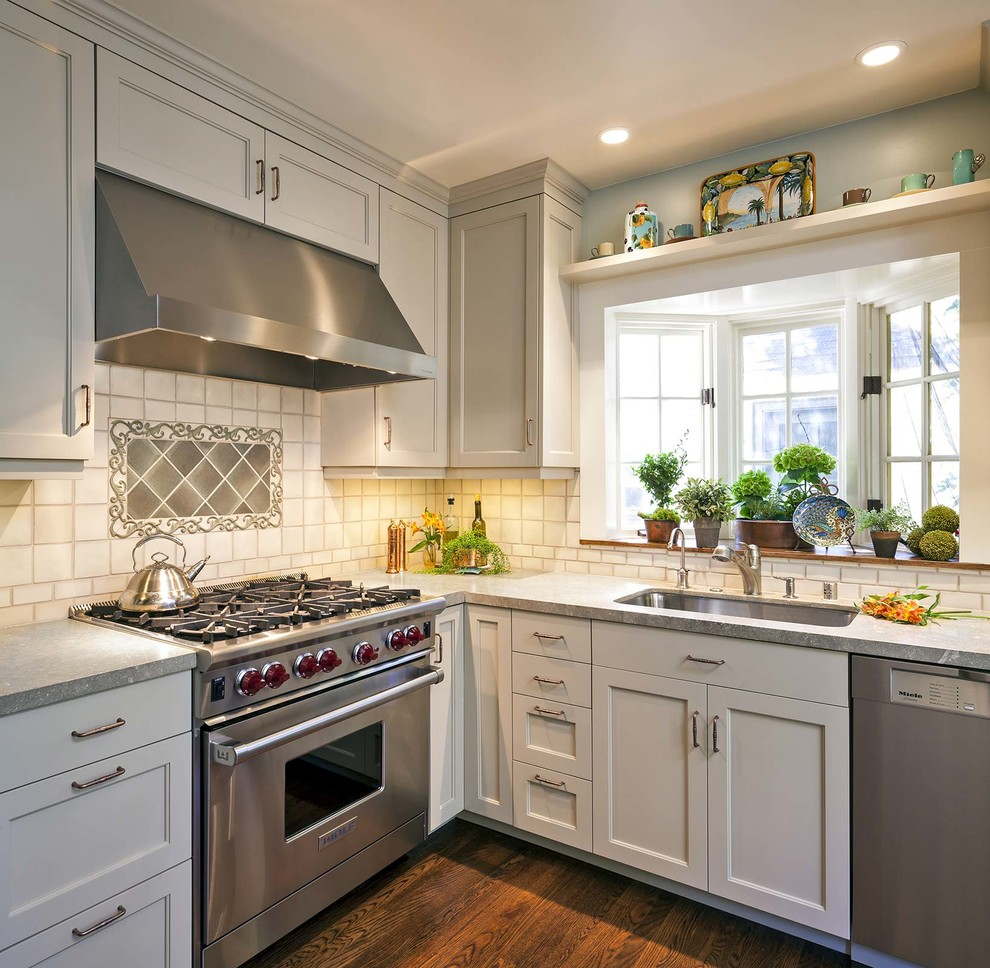 Elegant l-shaped dark wood floor kitchen photo in San Francisco with an undermount sink, shaker cabinets, white cabinets, white backsplash and stainless steel appliances