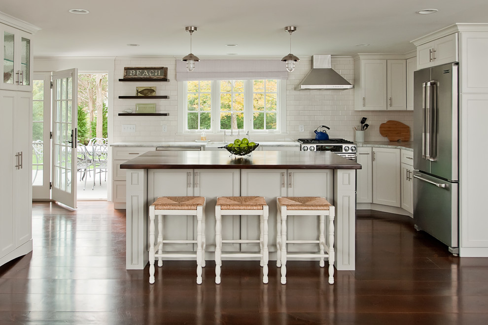 Kitchen - contemporary l-shaped kitchen idea in Boston with shaker cabinets, white cabinets, white backsplash, subway tile backsplash and stainless steel appliances