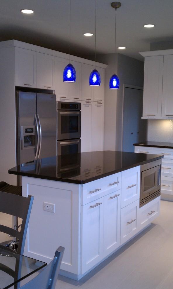 Foto de cocina actual, de tamaño medio, con puertas de armario blancas, electrodomésticos de acero inoxidable, una isla, armarios con paneles empotrados, encimera de granito, salpicadero blanco y salpicadero de azulejos de cerámica