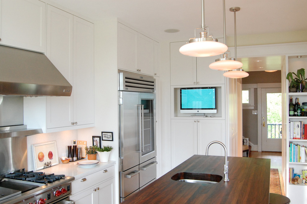 Elegant kitchen photo in Seattle with wood countertops