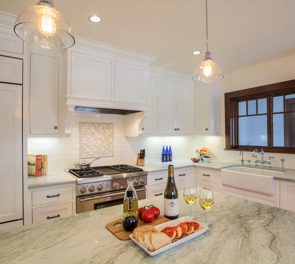 Kitchen - mid-sized traditional medium tone wood floor kitchen idea in Los Angeles with a farmhouse sink, shaker cabinets, quartzite countertops, beige backsplash, subway tile backsplash, stainless steel appliances, an island and white cabinets